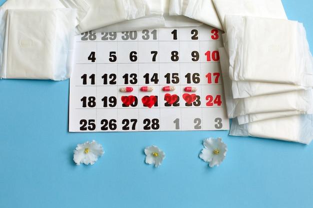Concepto del ciclo de la menstruación. calendario de menstruación con toallas sanitarias, píldoras anticonceptivas, flores.