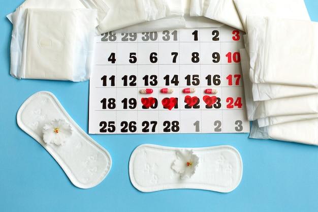 Concepto del ciclo de la menstruación. calendario de la menstruación con toallas sanitarias, píldoras anticonceptivas y flores.