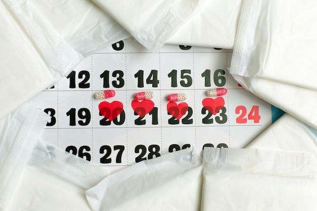 Concepto del ciclo de la menstruación. calendario de la menstruación con toallas sanitarias, píldoras anticonceptivas.