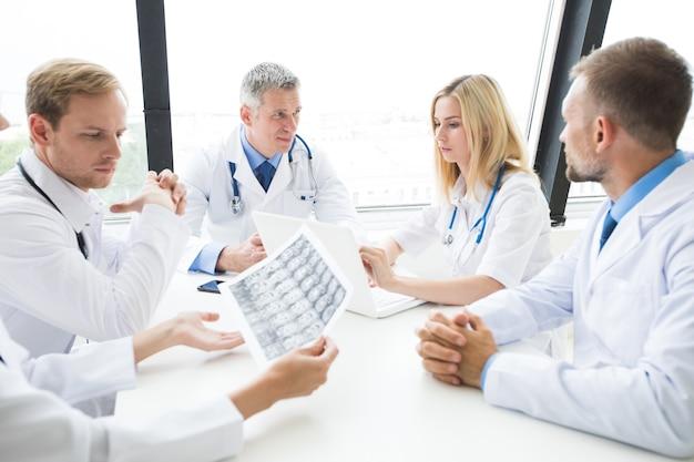 Concepto de clínica, personas, salud y medicina - grupo de médicos con exploración de rayos x del cerebro en el hospital