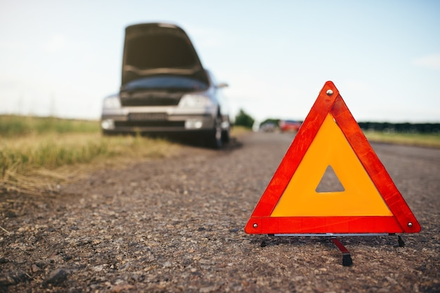 Concepto de coche roto, triángulo de avería en la carretera asfaltada. problema con el vehículo, señal de advertencia