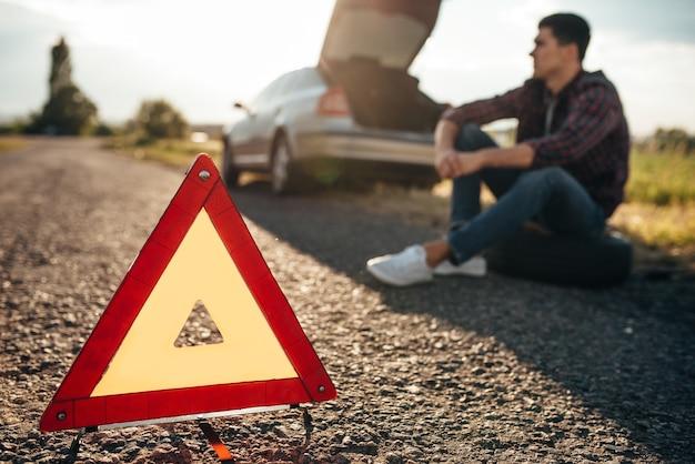 Concepto de coche roto, triángulo de avería en la carretera