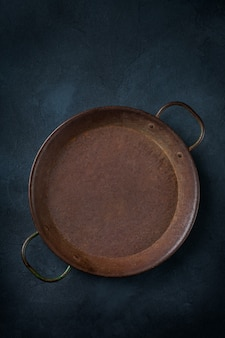 Concepto de cocina de alimentos. sartén para asar de hierro fundido vacía sobre un fondo oscuro. endecha plana, vista superior, espacio de copia