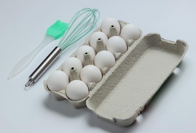 El concepto de cocina bandeja de cartón de huevos utensilios de cocina cepillo batidor sobre fondo blanco.
