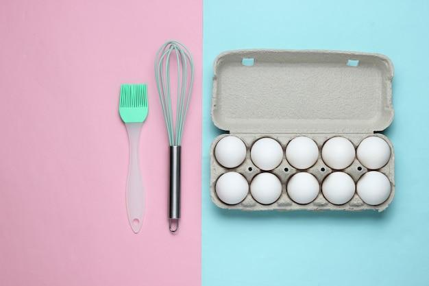 El concepto de cocina bandeja de cartón de huevos utensilios de cocina cepillo batidor sobre un fondo pastel bluepink