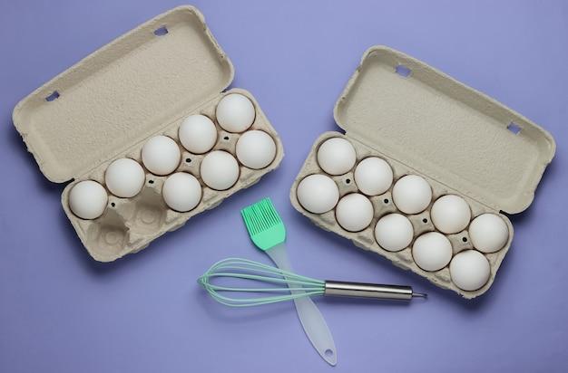 El concepto de cocina bandeja de cartón de huevos utensilios de cocina cepillo batidor sobre fondo púrpura