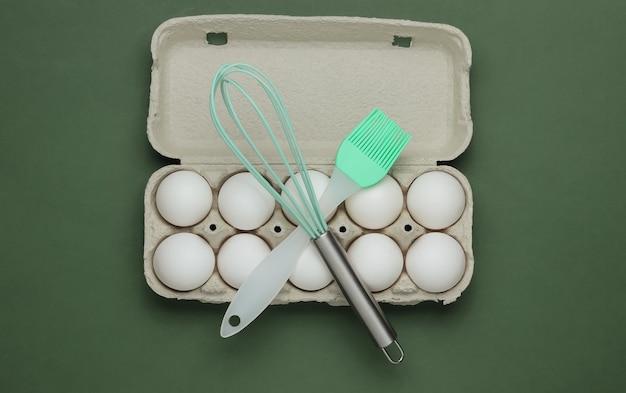 El concepto de cocina bandeja de cartón de huevos utensilios de cocina cepillo batidor sobre fondo verde