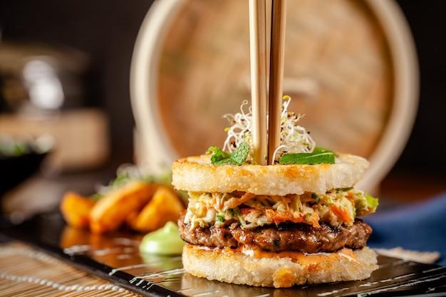 Concepto de cocina panasiática. hamburguesa de sushi japonesa hecha de pan de arroz, empanadas de carne de pollo y cerdo, lechuga y salsa de wasabi. sirviendo platos con papas fritas. copia espacio