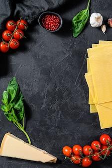 El concepto de cocinar lasaña. ingredientes, láminas de lasaña, albahaca, tomates cherry, parmesano, ajo, pimienta. vista superior. fondo copyspace