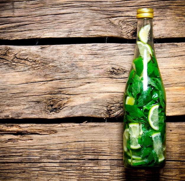 Concepto de cóctel mojito. botella de cóctel en una mesa de madera. espacio libre para texto. vista superior