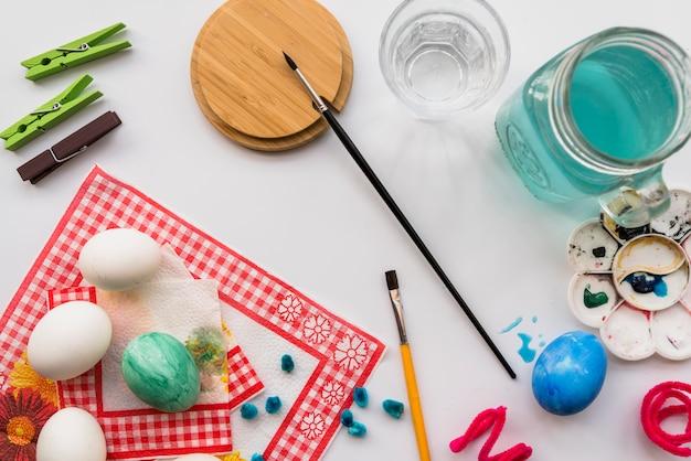 Concepto de colorear huevos cerca de paleta y pinceles