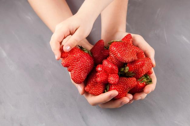 Concepto: comer frutas y verduras feas. la mano de los niños toma unas fresas maduras divertidas de forma inusual de manos femeninas. fondo gris, espacio de copia.