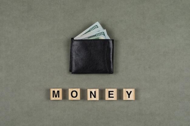 Concepto comercial y financiero con dinero en la billetera, cubos de madera en superficie plana gris endecha.
