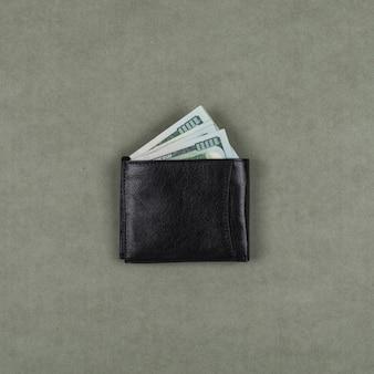 Concepto comercial y financiero con dólares en cartera en superficie plana gris endecha.