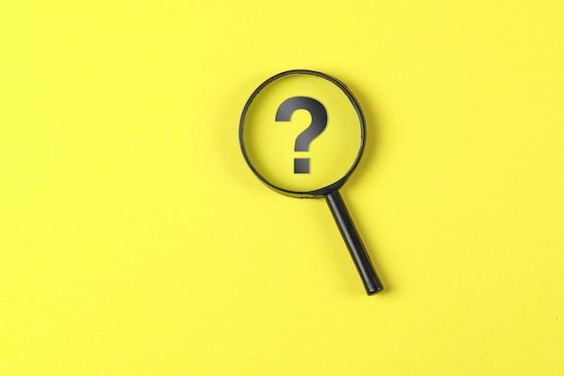 Concepto comercial y financiero con lupa, signo de interrogación sobre fondo amarillo plano lay.