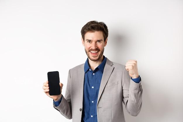 Concepto de comercio electrónico y compras en línea. hombre ganando dinero en internet, mostrando la pantalla del teléfono inteligente y el gesto del ganador, sonriendo satisfecho, de pie sobre fondo blanco.