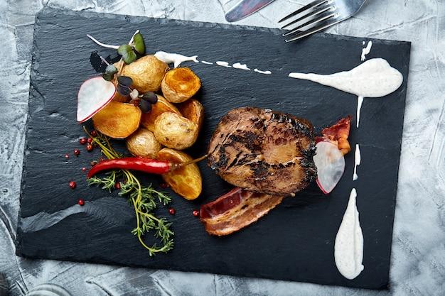 Concepto de comida. bistec con mini papas, espacio negro. vista desde arriba