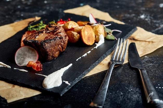 Concepto de comida. bistec con mini papas, espacio negro.