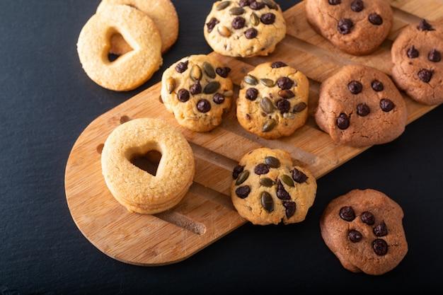 Concepto de comida casera galletas de mantequilla de azúcar sobre tabla de madera sobre placa de piedra pizarra negra con espacio de copia