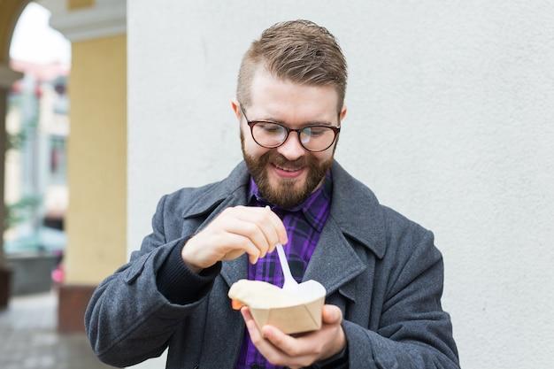 Concepto de comida chatarra, comer y estilo de vida - joven con comida come en las calles de la ciudad.
