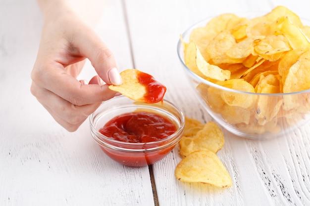 Concepto de comida chatarra grasa, mujer mantenga papas fritas con salsa de tomate