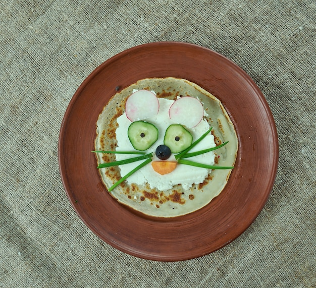 Concepto de comida creativa de gato hecho de panqueques, brynza, pepino y aceitunas. menú infantil