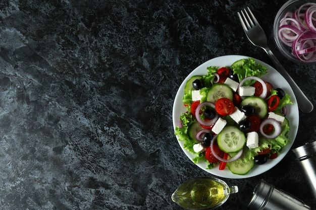 Concepto de comida deliciosa con ensalada griega sobre fondo negro ahumado