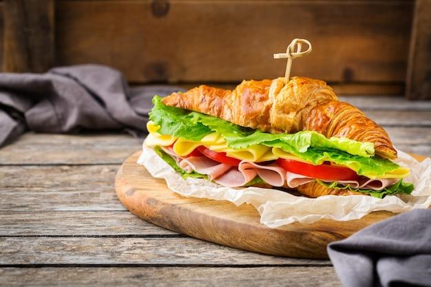 Concepto de comida, desayuno, mañana y almuerzo. sándwich de croissant fresco con jamón, queso, lechuga y tomate en una mesa de madera