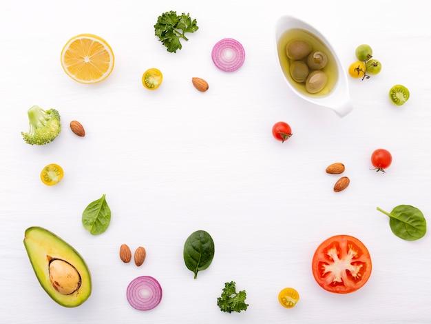 El concepto de la comida y de la ensalada con endecha plana de los ingredientes crudos en de madera blanco.