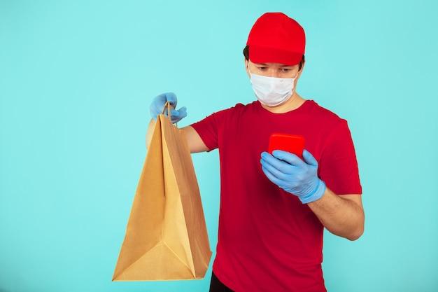 Concepto de comida de entrega. mensajero de hombre en la ropa roja con bolsa de artesanía con trato y usando el teléfono.