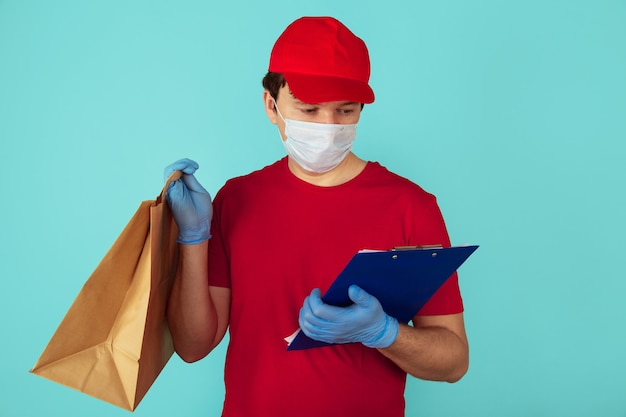 Concepto de comida de entrega. mensajero de hombre en la ropa roja con bolsa de artesanía con trato y uso de tableta.