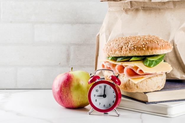 Concepto de comida escolar saludable, bolsa de papel con almuerzo, manzana, sándwich, libros y reloj despertador