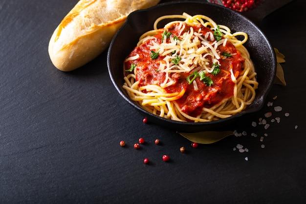 Concepto de comida espaguetis caseros boloñesa en hierro fundido.
