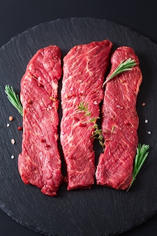 Concepto de comida filete de carne cruda orgánica filete de res en piedra de pizarra negra