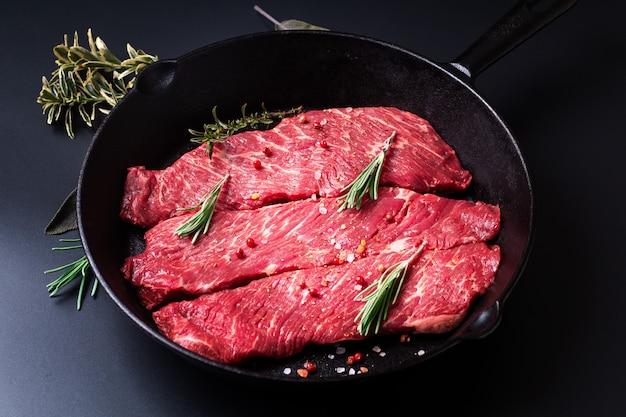 Concepto de comida filete de carne cruda orgánica filete en sartén sartén de hierro sobre negro
