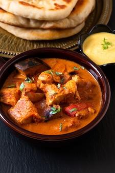 Concepto de comida hecho en casa con pollo al curry de masala tandoori con pan naan y salsa de yogurt.