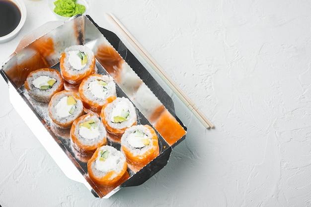 Concepto de comida japonesa. catering, diversos tipos de sushi philadelphia rolls y rollitos de gambas al horno, en piedra blanca