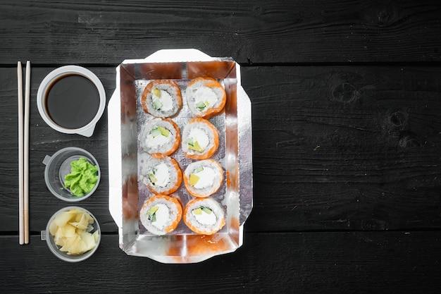 Concepto de comida japonesa. catering, diversos tipos de sushi philadelphia rolls y rollitos de gambas al horno, sobre mesa de madera negra