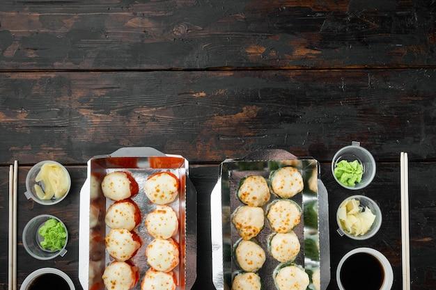 Concepto de comida japonesa. catering, diversos tipos de sushi philadelphia rolls y rollitos de gambas al horno, en la vieja mesa de madera oscura.