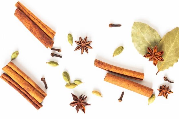 Concepto de comida mezcla de especias de anís orgánico, canela, laurel y vainas de cardamomo en blanco