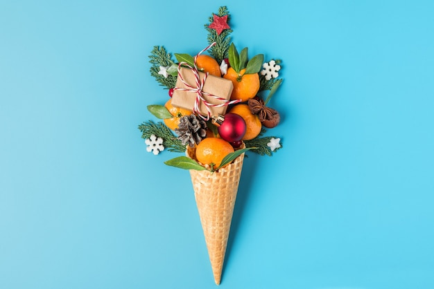 Concepto de comida navideña. frutas mandarina, caja de regalo y adornos navideños en cono de helado waffle sobre fondo azul. vista superior. endecha plana