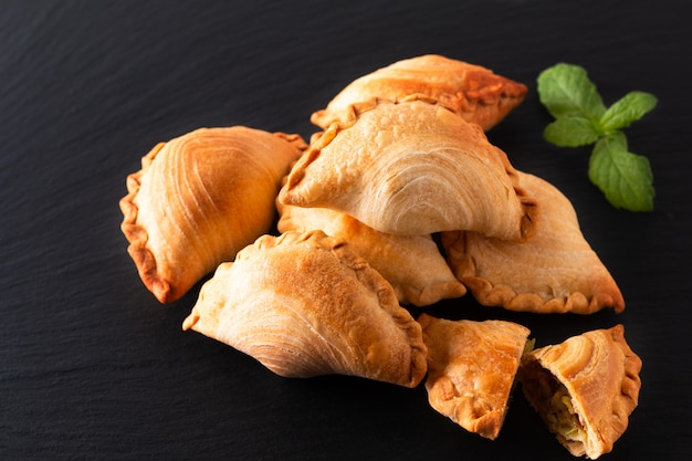 Concepto de comida de origen del sudeste asiático pollo casero curry puffs sobre fondo de piedra pizarra negra con espacio de copia