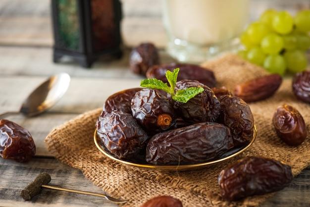 El concepto de comida de ramadán. linterna de ramadán con leche, dátiles frutales, uva y hojas de menta.