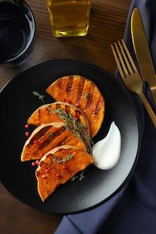 Concepto de comida sabrosa con calabaza al horno sobre fondo de madera.