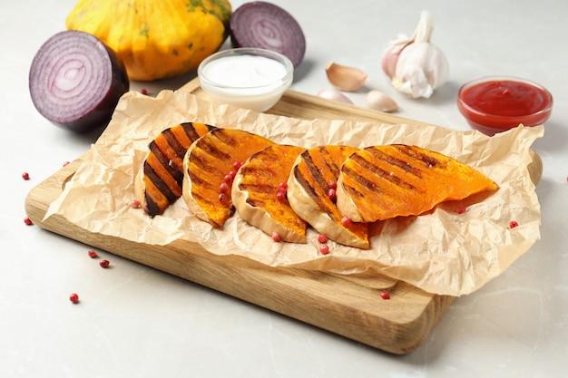 Concepto de comida sabrosa con calabaza al horno sobre fondo de textura ligera.