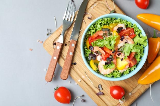 Concepto de comida sabrosa con ensalada de camarones sobre fondo gris