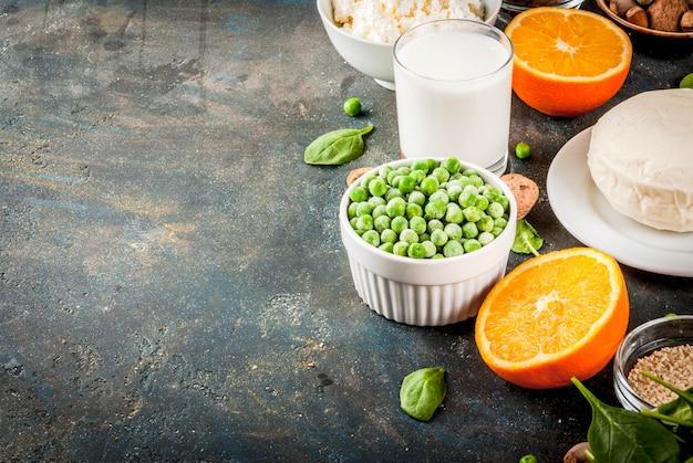 Concepto de comida saludable. conjunto de alimentos ricos en calcio: productos lácteos y veganos de ca, espacio de copia de superficie azul oscuro