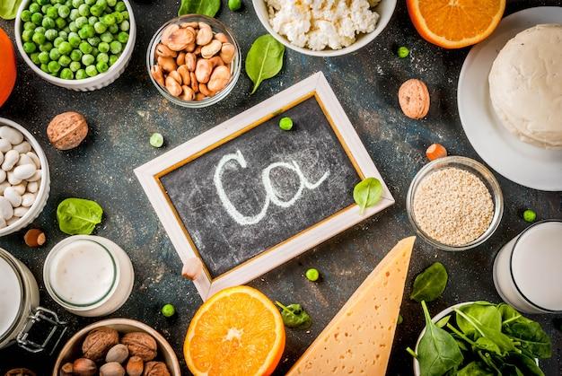 Concepto de comida saludable. conjunto de alimentos ricos en calcio - productos lácteos y veganos ca fondo azul oscuro