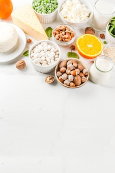 Concepto de comida saludable. conjunto de alimentos ricos en calcio - productos lácteos y veganos ca fondo de mármol blanco