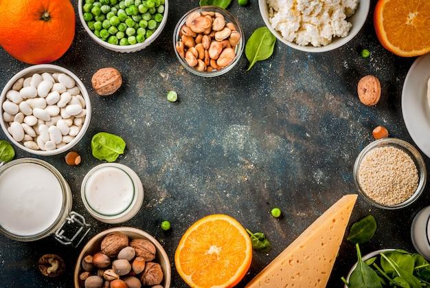 Concepto de comida saludable. conjunto de alimentos ricos en calcio - productos lácteos y veganos ca marco de fondo azul oscuro
